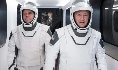 NASA astronauts Bob Behnken and Doug Hurley in their SpaceX spacesuits walking down a white corridor.