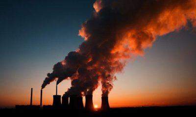 Distant shot at dusk of large power station emitting CO2.