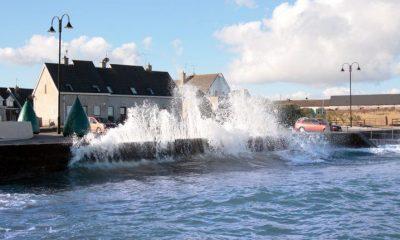 Waves crashing against a coastal wall beside a house.
