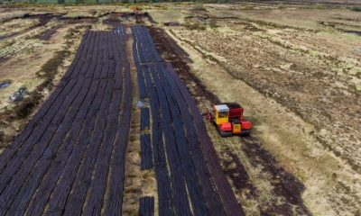 Aerial view of a tractor harvesting peat from a bog in the midlands.