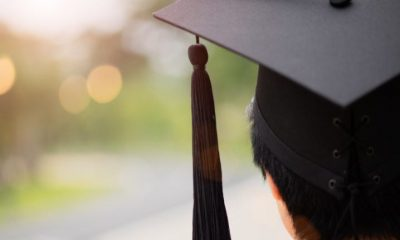 Rear view of student graduating, wearing a black cap with a tassle.