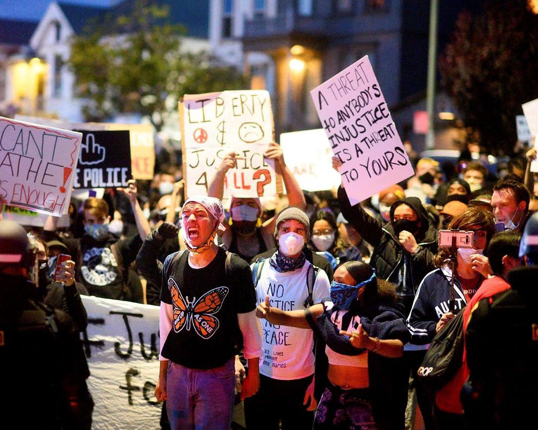 In this May 29, 2020, photo, demonstrators face off against police officers in Oakland, Calif. while protesting the Monday death of George Floyd, a handcuffed black man in police custody in Minneapolis.