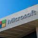 The Microsoft logo displayed on an office building under a blue sky.