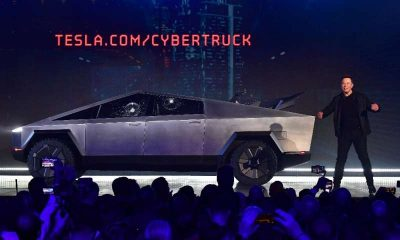 Tesla co-founder and CEO Elon Musk on stage with  the newly unveiled all-electric battery-powered Tesla Cybertruck with broken g