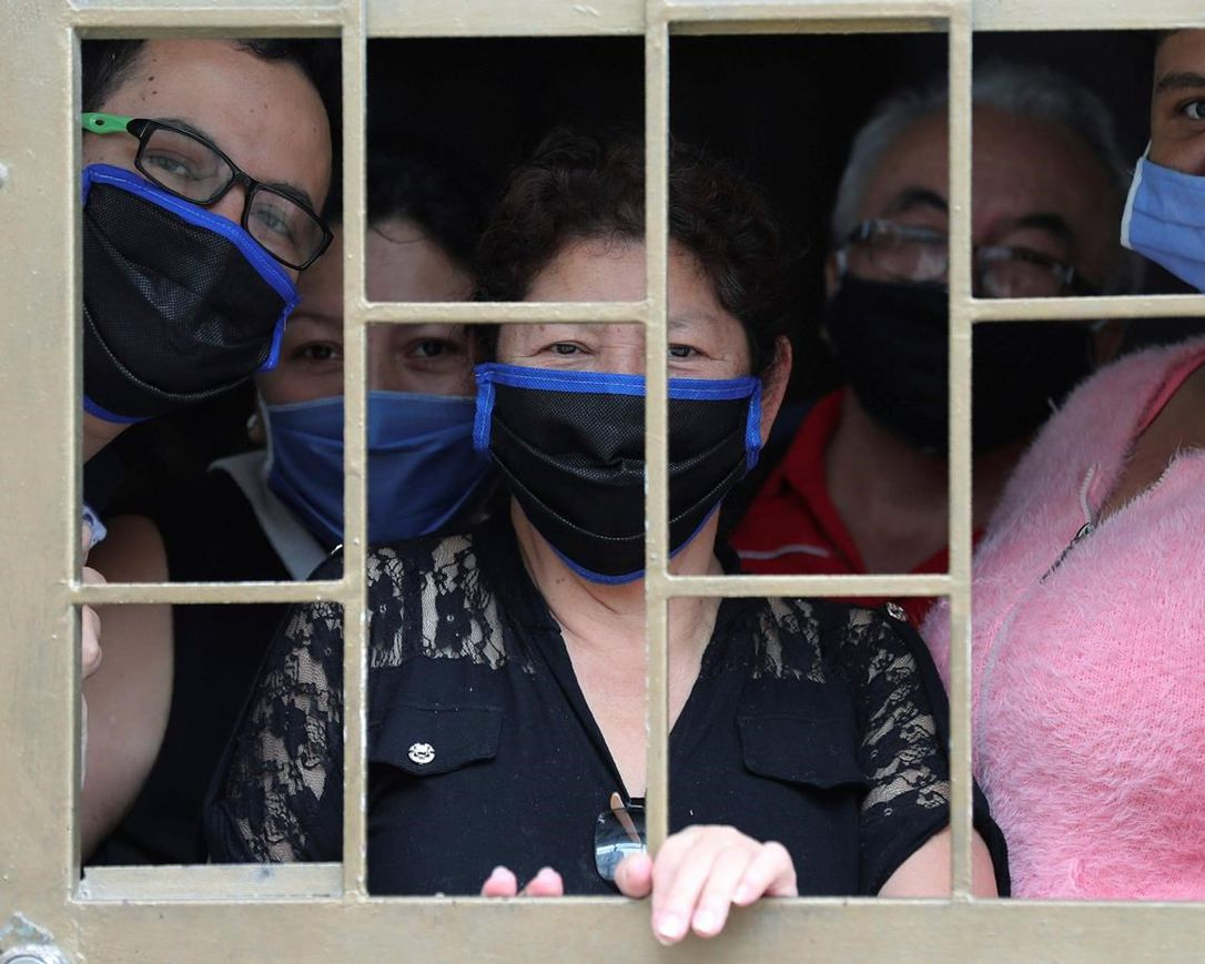 A family peers from the window of their home as they wait to receive boxes of free food, during a lockdown to curb the spread of the new coronavirus, in Bogota, Colombia, Monday, May 4, 2020. The U.N. World Food Program is warning that upward of at least 14 million people could go hungry in Latin America as the coronavirus pandemic rages on, shuttering people in their homes, drying up work and crippling the economy.