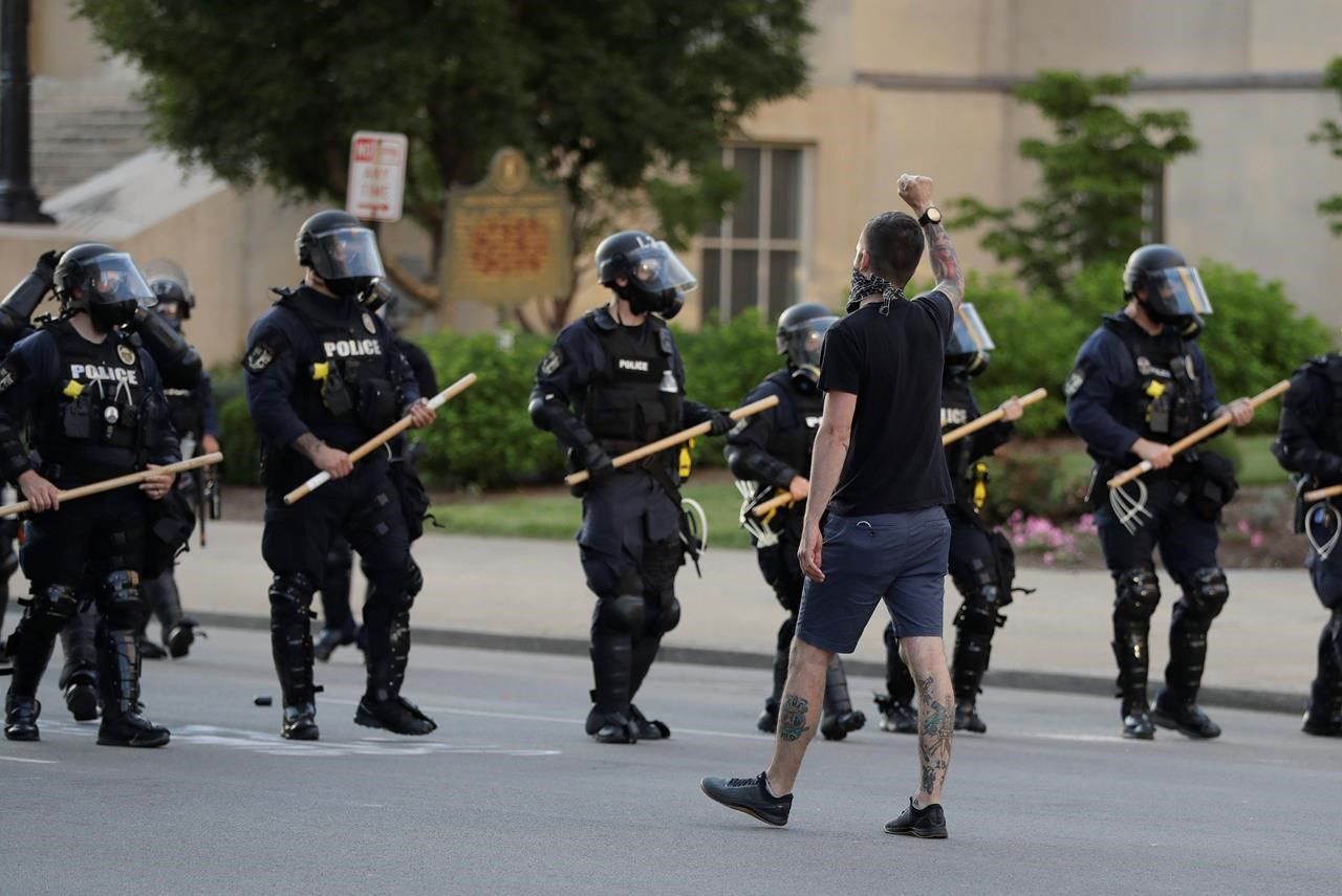 A protester walks with police officers during a protest over the deaths of George Floyd and Breonna Taylor, Saturday, May 30, 2020, in Louisville, Ky. Breonna Taylor, a black woman, was fatally shot by police in her home in March.