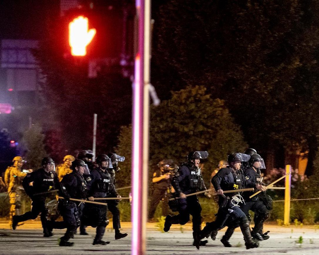 Police and Kentucky National Guard troops chase protesters as they flee toward a fence Sunday, May 31, 2020, in a parking lot at the corner of East Broadway and South Brook Street in downtown Louisville, Kentucky.