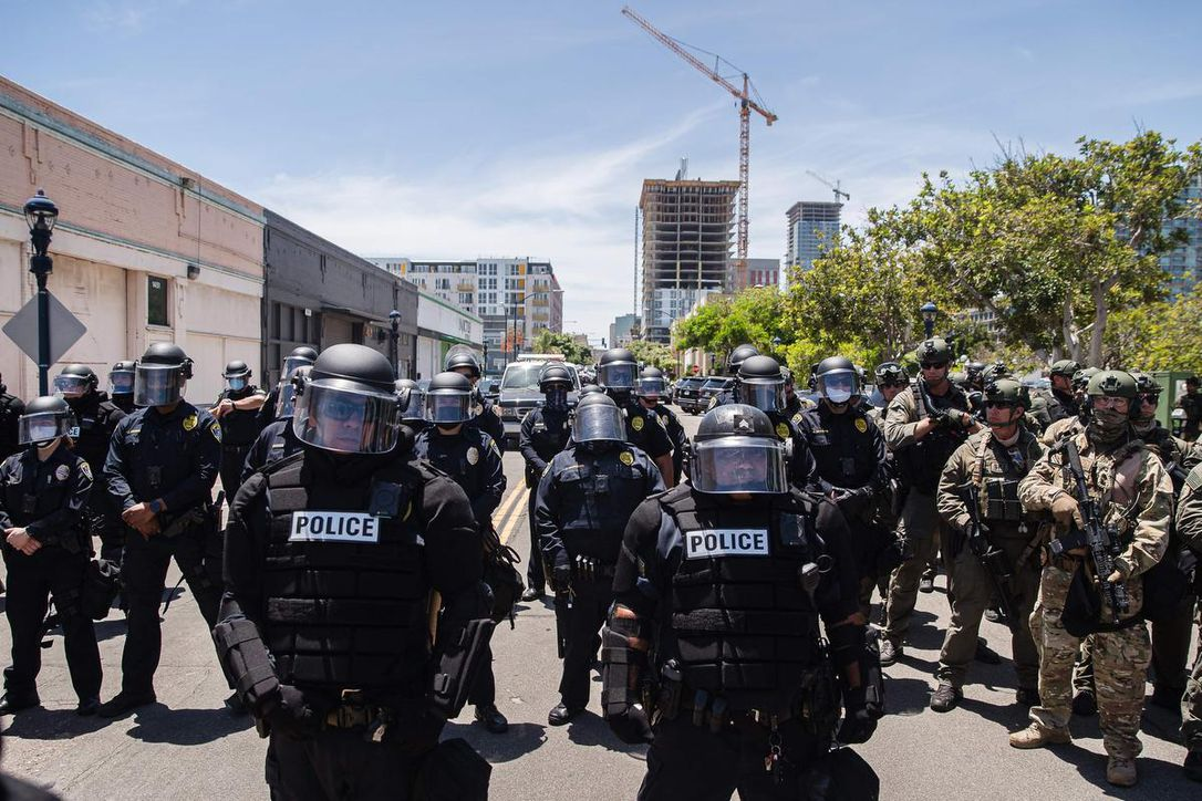 San Diego Police officers (L) in riot gear and a special tactics group (R) face-off with demonstrators in downtown San Diego, California as people gather to protest against the death of Minneapolis man George Floyd.