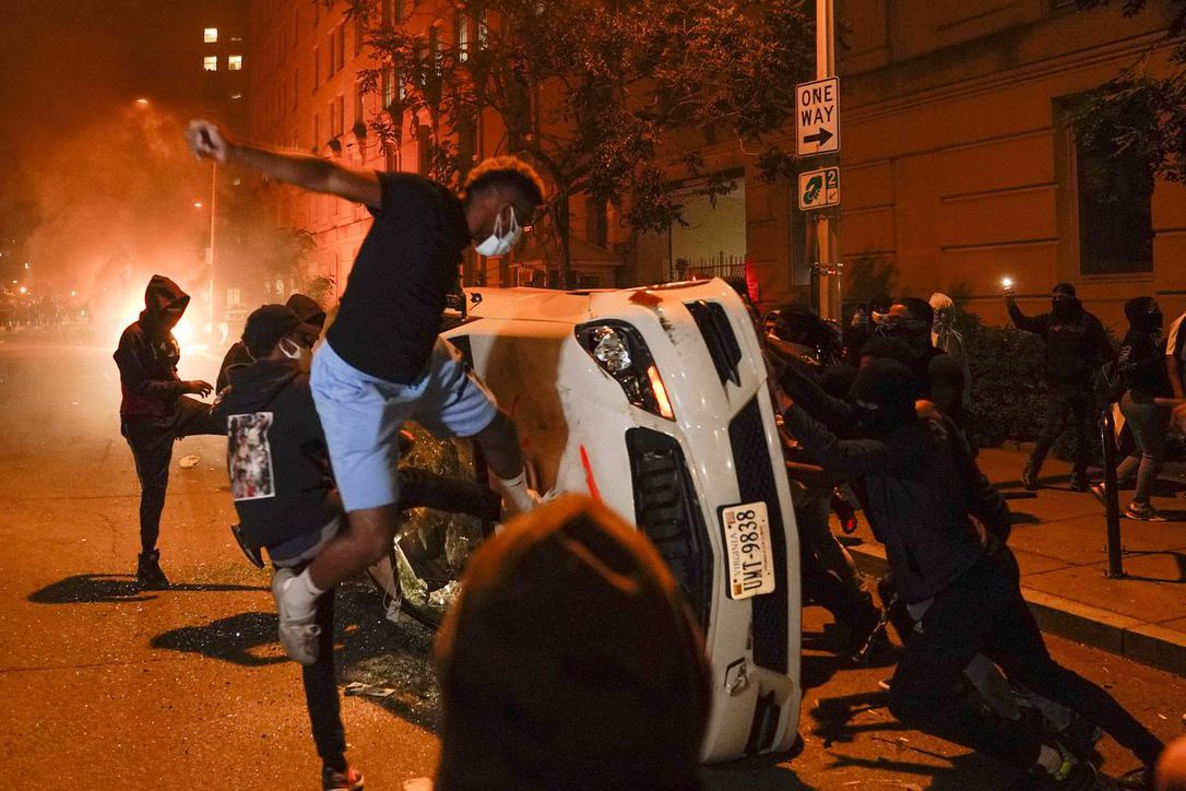 Police fired tear gas near the White House on Sunday night to dissuade U.S. protesters who had smashed the windows of prominent buildings, overturned cars and set fires, with smoke seen rising from near the Washington Monument.