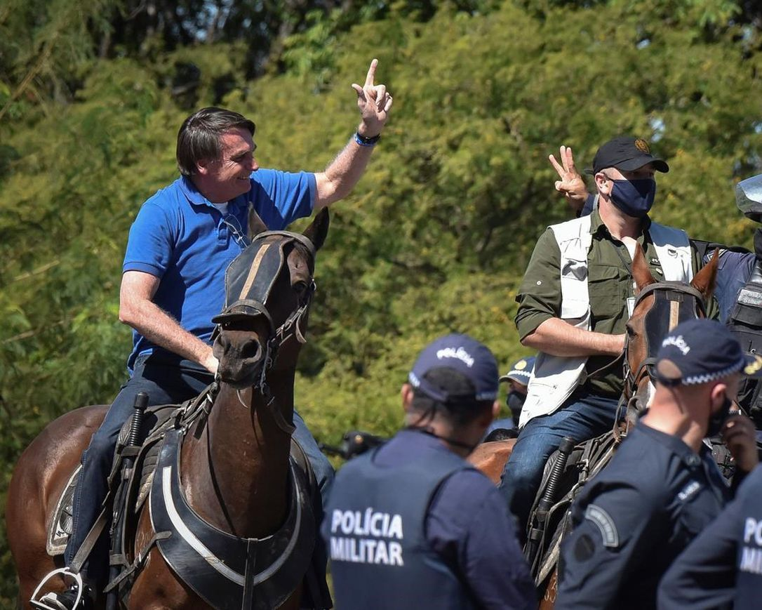 Brazil's President Jair Bolsonaro rides a horse greeting supporters outside the presidential palace in Brasilia, Brazil, Sunday, May 31, 2020. Bolsonaro mounted a horse from police that were guarding supporters of his government gathered outside the Planalto Palace.