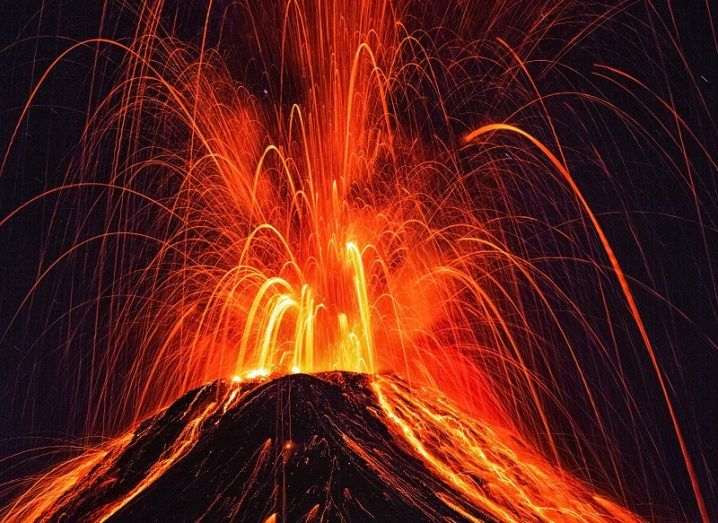 An erupting volcano spewing bright red lava at night.