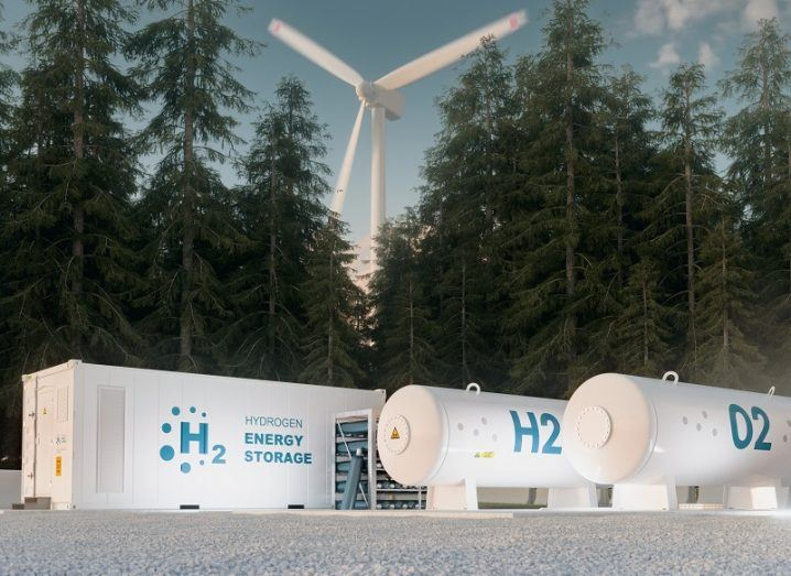 Concept of a hydrogen fuel production station beside a forest and a wind turbine.
