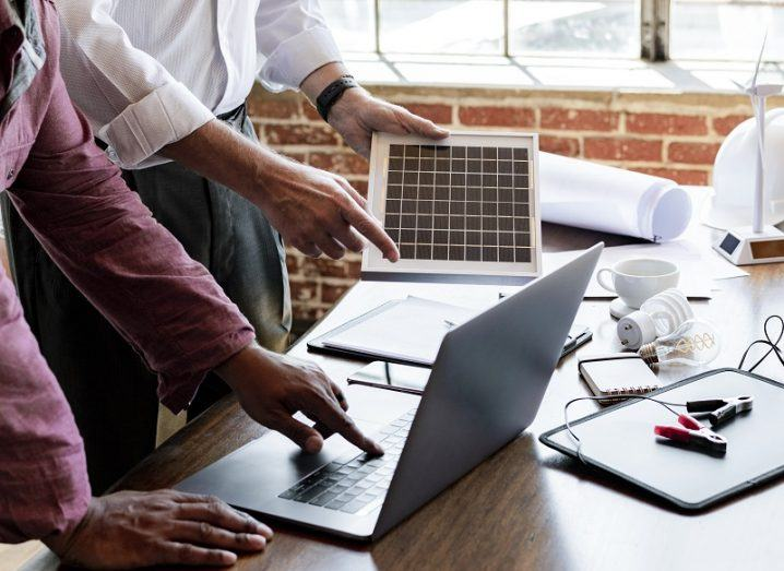 Pair of engineers at a table with a laptop, solar panel and small wind turbine on it.