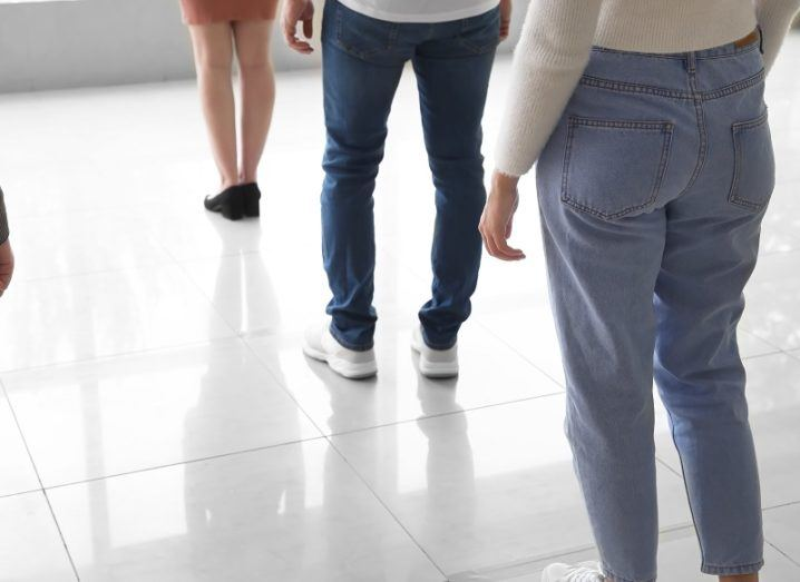 Queue of people social distancing in a room with white floor tiles.