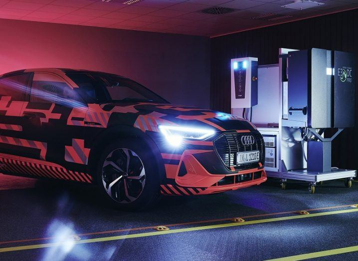 An Audi E-tron car coloured black and neon red, with its lights on beside a bidirectional charging station.