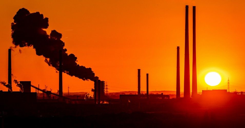 The sun goes down behind chimneys at a coal plant in Duisburg, Germany on June 28, 2019. (Photo: Marcel Kusch/dpa/picture alliance via Getty Images)