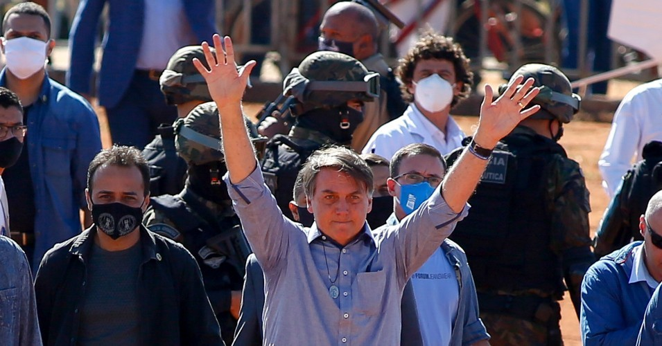 Brazilian President Jair Bolsonaro (C) waves to supporters during the inauguration of a field hospital in Aguas Lindas, in the State of Goiais, Brazil, on June 5, 2020 amid the Covid-19 pandemic.
