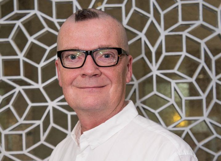 Headshot of Johan Ericsson wearing black glasses and a white shirt against a gold and white wall.