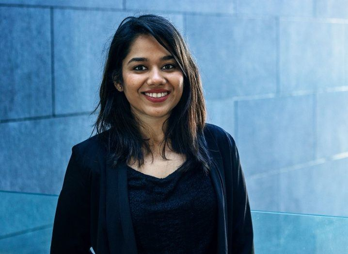 Nidhi Kedia-Mehta smiling in a black top against a blue-brick wall background.