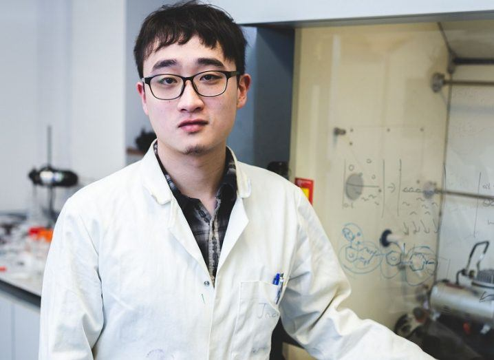 Dr Yikai Xu in a white lab coat and glasses in a lab.