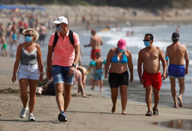 Several people walk along the beach wearing face masks