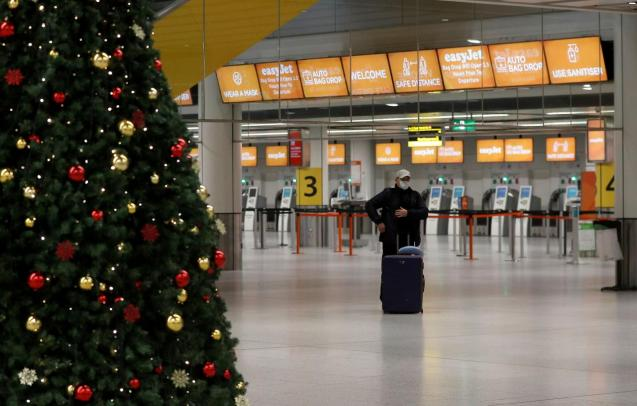 A passenger stands in an almost empty check-in area at Gatwick Airport