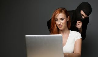 Red-headed white woman types on laptop while menacing figure wearing balaclava looks over her shoulder.